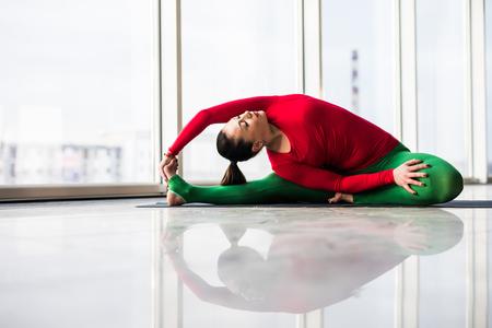 ushtrasana: Djanu-shirasana. Beautiful yoga woman practice in a big window hall background. Yoga concept. Stock Photo