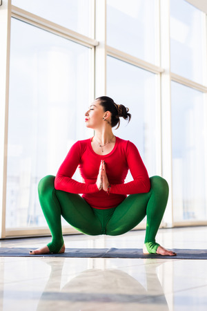 Kakasana.  Beautiful yoga woman practice in a big window hall background. Yoga concept.