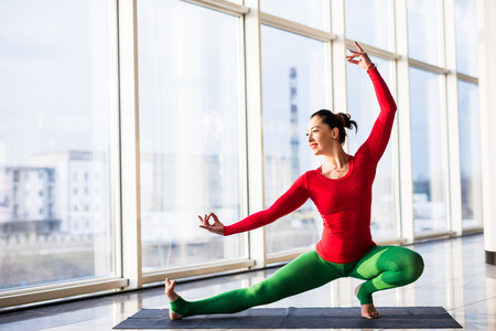 Virabadrasana. Beautiful yoga woman practice in a big window hall background. Yoga concept.
