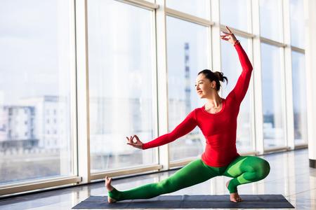 hasta: Virabadrasana. Beautiful yoga woman practice in a big window hall background. Yoga concept.