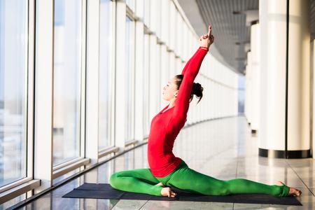 ushtrasana: Beautiful yoga woman practice in a big window hall background. Yoga concept.