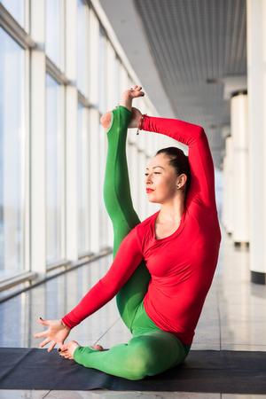 Beautiful yoga woman practice in a big window hall background. Yoga concept.