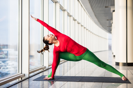 ardha: Utthita parsvakonasana. Beautiful yoga woman practice in a big window hall background. Yoga concept.