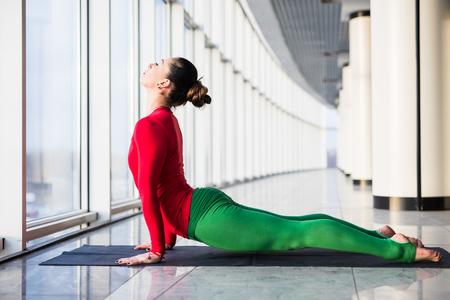 ushtrasana: Urdhva mukha svanasana. Beautiful yoga woman practice in a big window hall background. Yoga concept.