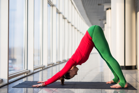 Ardha shirshasana. Beautiful yoga woman practice in a big window hall background. Yoga concept.