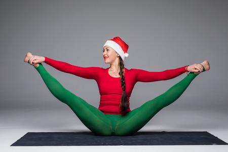 sukhasana: Beautiful yoga woman in santa hat  practice yoga poses on grey background. Yoga concept. Stock Photo