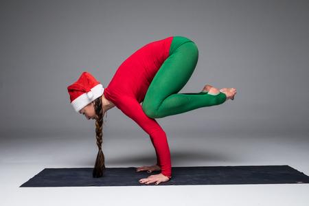 hasta: Beautiful yoga woman in santa hat  practice yoga poses on grey background. Yoga concept. Stock Photo
