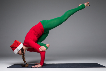 Beautiful yoga woman in santa hat  practice yoga poses on grey background. Yoga concept. Stock Photo
