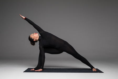 Utthita parsvakonasana. Beautiful yoga woman practice yoga poses on grey background. Yoga concept. Stock Photo