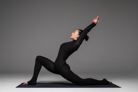 hasta: Anjaneyasana. Beautiful yoga woman practice yoga poses on grey background. Yoga concept.