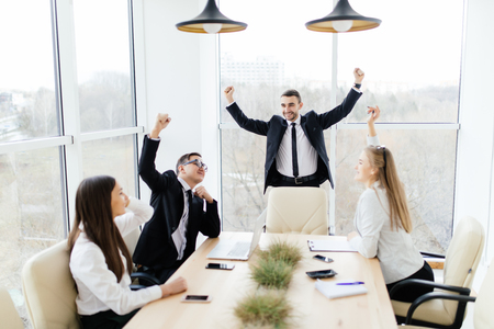aplaudiendo: Business meeting. Business people in formalwear celebrate victory  while sitting together at the table