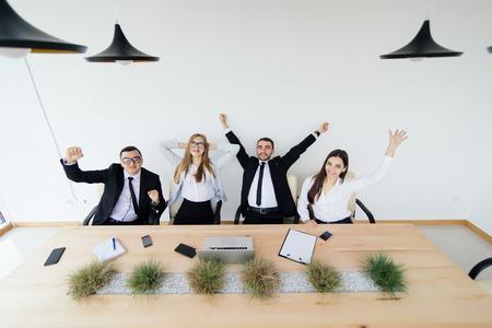 aplaudiendo: Corporate work. Business people celebrate victory in meeting room