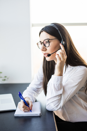 Businesswoman with headset in call center in modern office