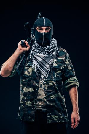 Terrorist attack. Terrorist with gun on black background