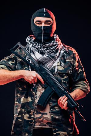 Terrorist with gun on  dark background Stock Photo