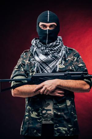 Terrorist with gun on red background