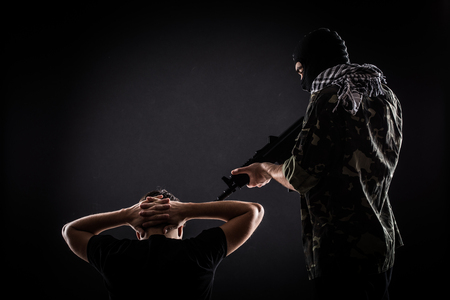 Terrorist with gun on hostage on black background