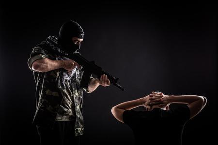 iraq: Terrorist with gun on hostage on black background