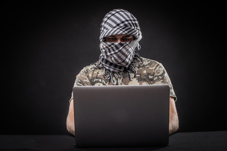 Hacker terrorist atack network from laptop over black background Stock Photo