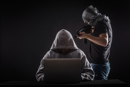 spyware: Terrorist  attack  hacker with gun work at laptop.