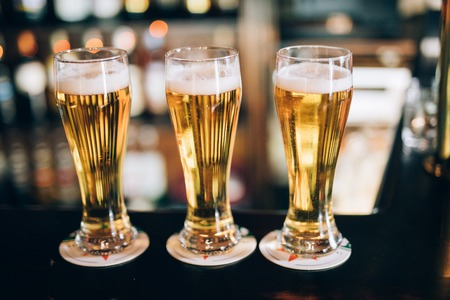 cup four: Three glasses with beers in a pub background
