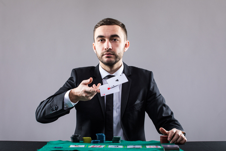 poker player: Poker player, on a grey background, throwing two ace cards. Stock Photo