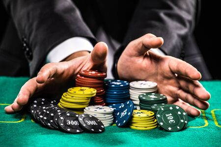 stakes: casino, gambling, poker, people and entertainment concept - close up of poker player with chips at green casino table