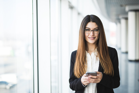 sidewalk talk: Young woman with mobile phone in the office against panoramic windows Stock Photo