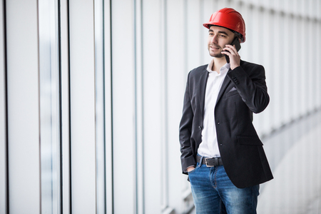 Engineer talking on the phone against panoramic windows