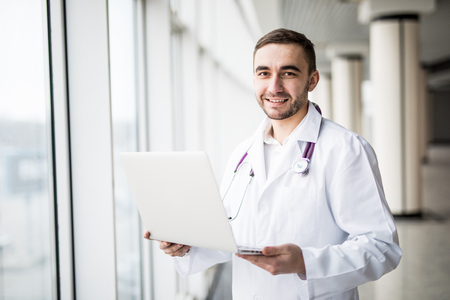 attractive young medical worker using laptop isolated on white background
