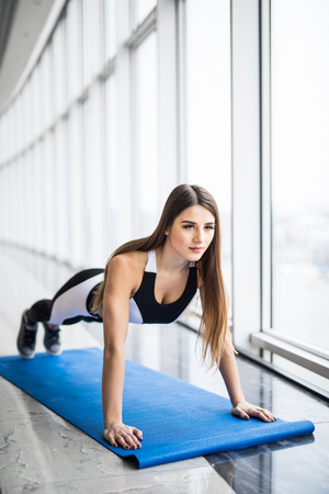 Working her core muscles. Full length of young beautiful woman in sportswear doing plank while standing in front of window Stock Photo