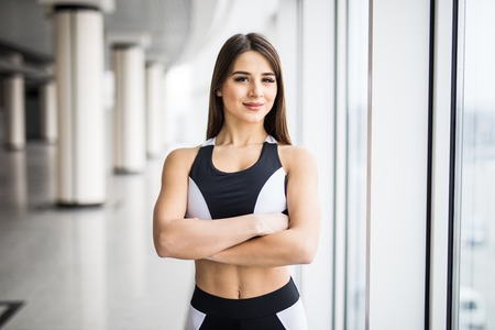 Woman with crossed hands in sportswear looking at camera while standing in front of window at gym