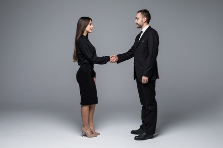 Business partners handshake on gray background. Contract