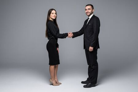 Business partners handshake and look at camera on gray background Stock Photo