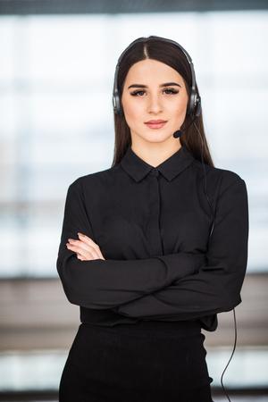 eslogan: Retrato de operador de teléfono de atención al cliente alegre sonriente en el auricular contra el fondo de la oficina