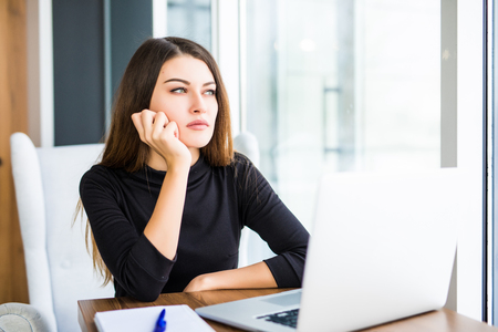 ノート パソコンでの作業とコンピューターの画面を凝視オフィスで退屈若い女性