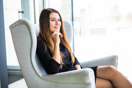 Attractive young woman sitting on a chair in a cafe