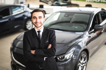 assistent: Handsome young classic car salesman standing at the dealership in front of new car