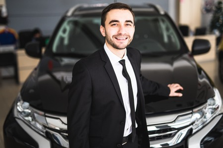 assistent: Handsome young classic car salesman standing at the dealership Stock Photo