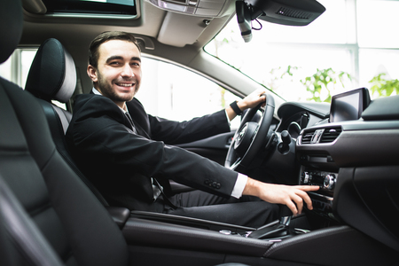 close up of young man in suit driving car and switching some button on panel of car and smile