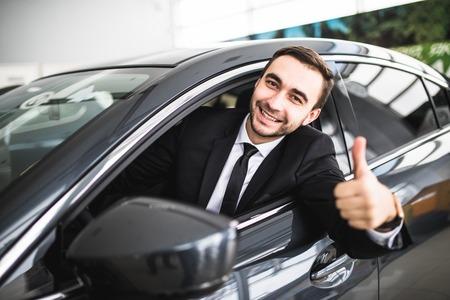 カメラ ウィンドウの上に彼の車で親指を現して微笑みのビジネスマン