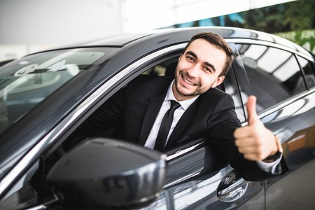 Businessman smiling at camera showing thumbs up in his car over window Stockfoto