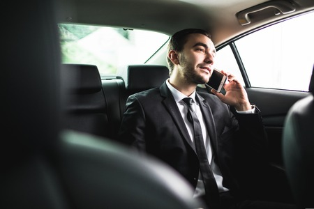 Businessman on call in car, smiling on passanger seat