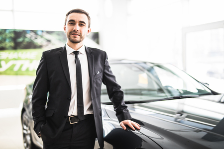assistent: Professional salesman smiling in front of a new car at the dealership profession occupation job owning buy retail luxury lifestyle concept Stock Photo