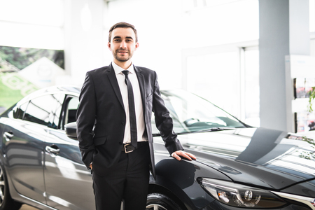 assistent: relaxed young businessman with hands crossed in front of car saloon. Stock Photo