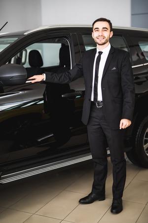 車近くに立っているスーツでハンサムな青年実業家のイメージ 写真素材