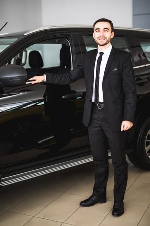 Image of handsome young businessman in suit standing near car