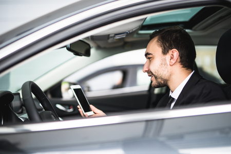 line lines luxury meeting: Businessman in car reading message on smartphone Stock Photo