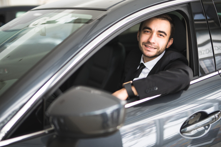 happy smiling driver in the car, portrait of young successful business man over window of car
