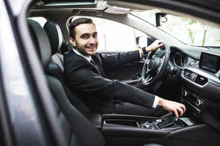 輸送、ビジネス旅行、宛先および人々 のコンセプト - 車の運転のスーツの若者のクローズ アップ 写真素材